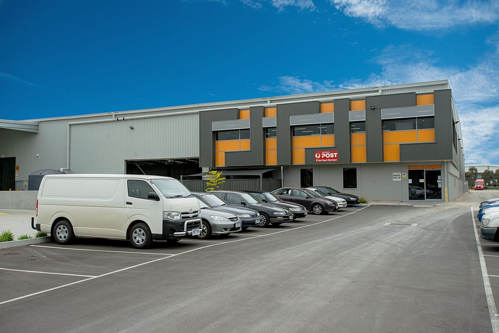 View of parking lot with vans with parcel handling facility in background