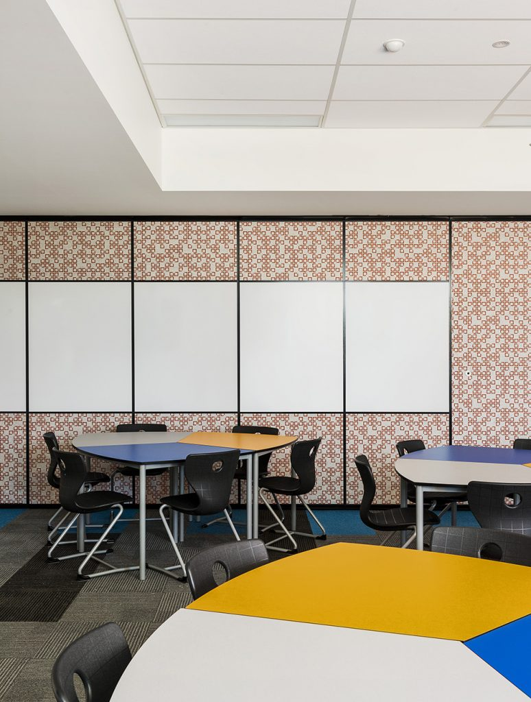 inside of new learning centre classroom which contains circular tables and fixed whiteboards