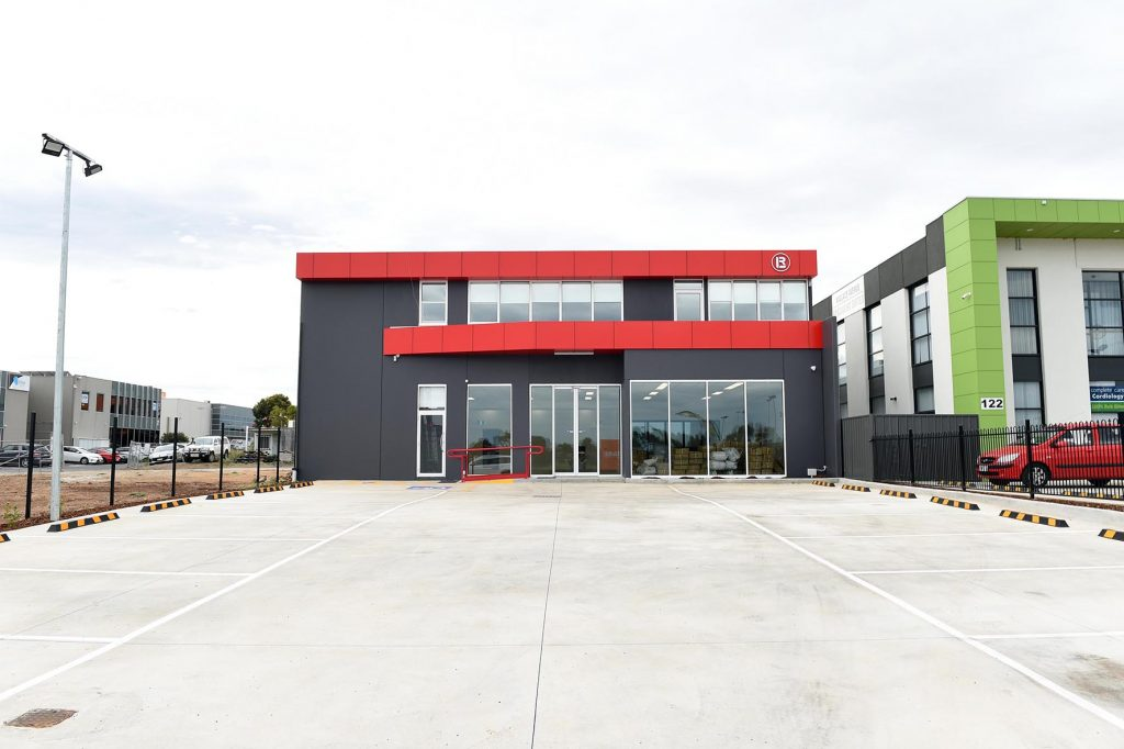 red and grey precast concrete walls and large glass windows at front of building. Green and white building next door