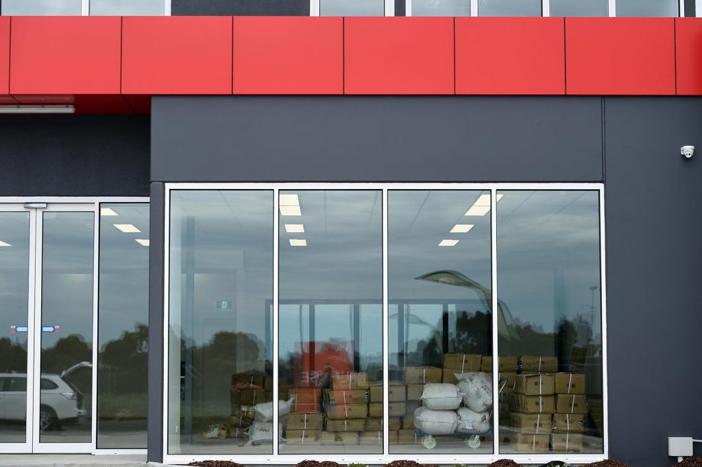 Red and grey precast concrete walls and large glass windows at front of Wanxi convenience store