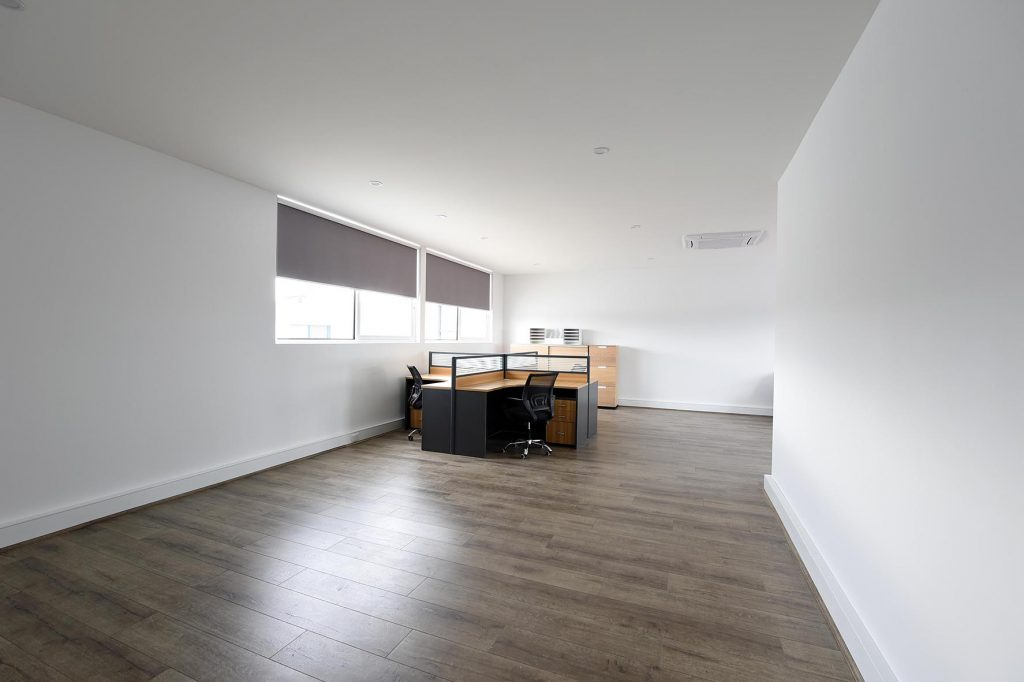 Hardwood floors and white walled room with table in the center