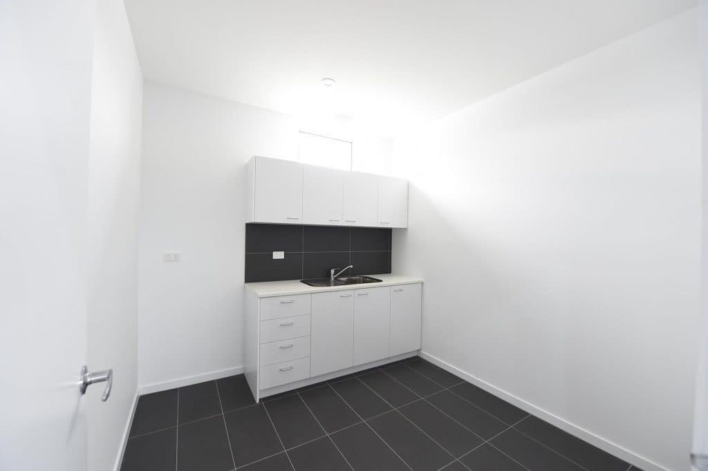 Kitchen area with grey floor tiles and black splash back