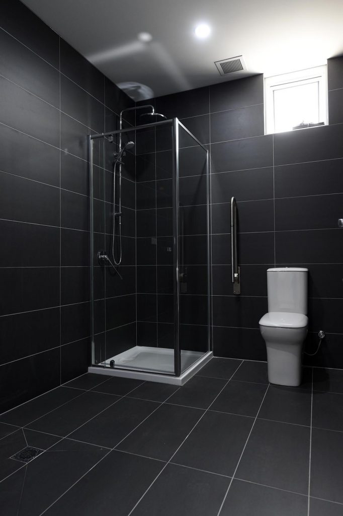 Toilet and shower with grey floor tiles
