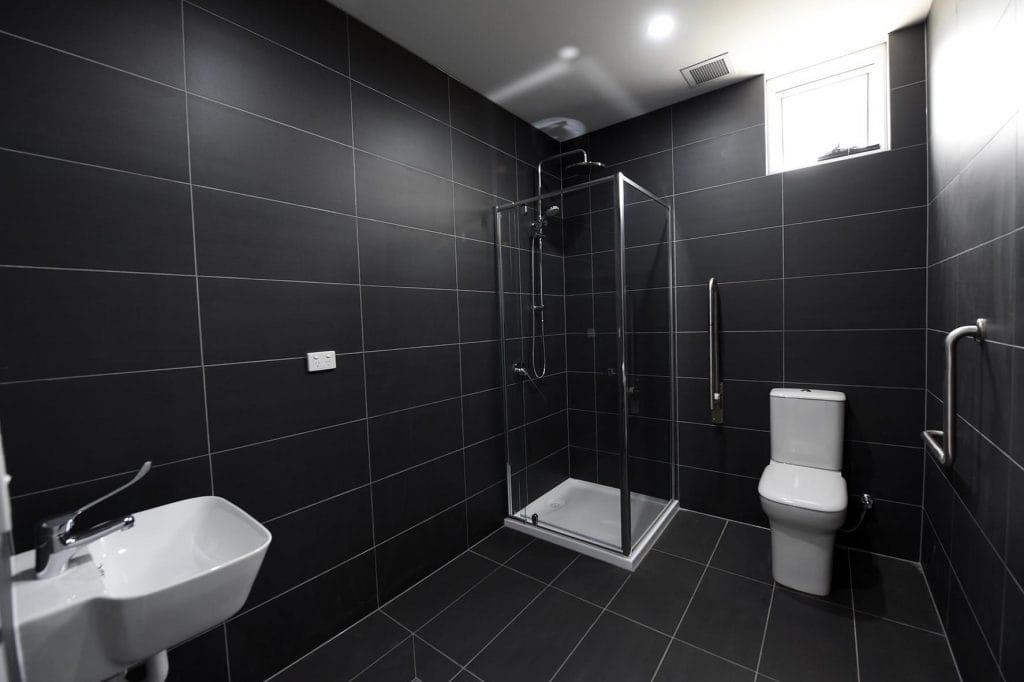 Toilet, shower and sink with grey floor tiles