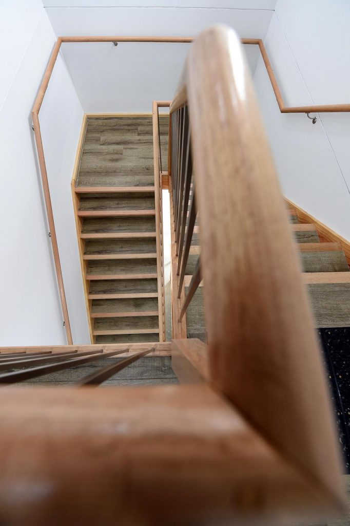 Looking down the hardwood stairs with wooden railing