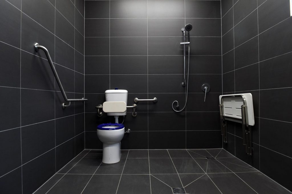 Disabled toilet facilities decorated with grey tiles on the floor and walls