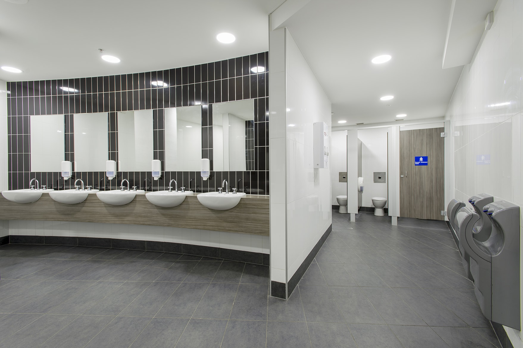 Brown tiles on wall with individual sinks in bathroom at Hisense area of Melbourne Park