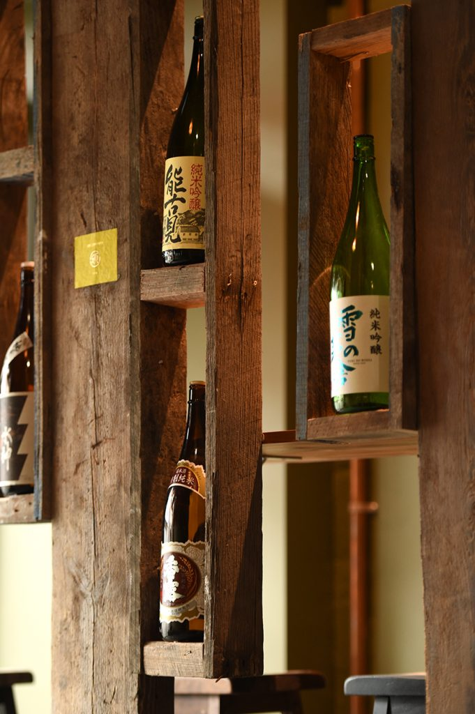 Saki bottles in worn wooden traditional looking Japanese shelf