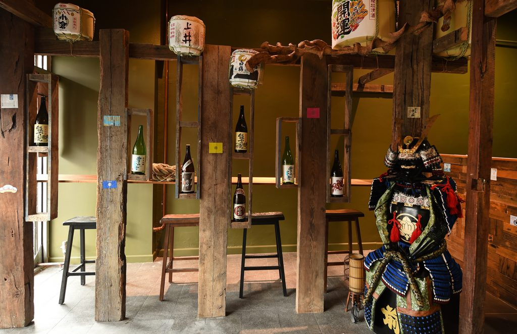 Saki bottles in shelves and a kabuki character holding a sword in front