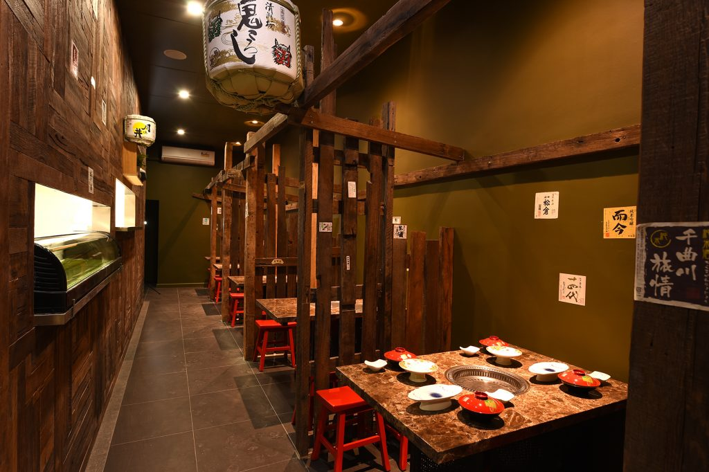 Booth seat of Kaiseki Japanese Restaurant with plates and cutlery decorating table