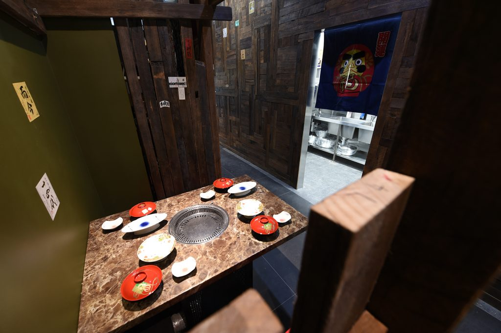 Marble table with red and white plates and Yaki nikku cooker in centre