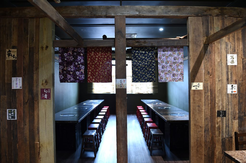 Wooden columns and traditional Japanese curtains decorate the dining area