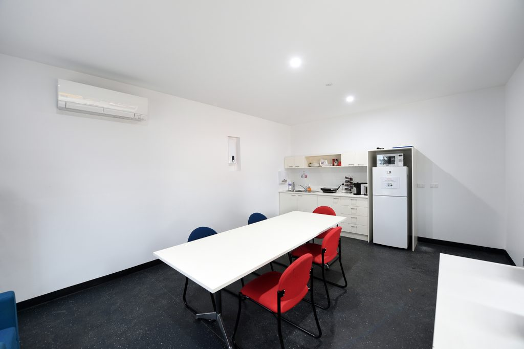 A white table and four red chairs inside the dining area of the warehouse