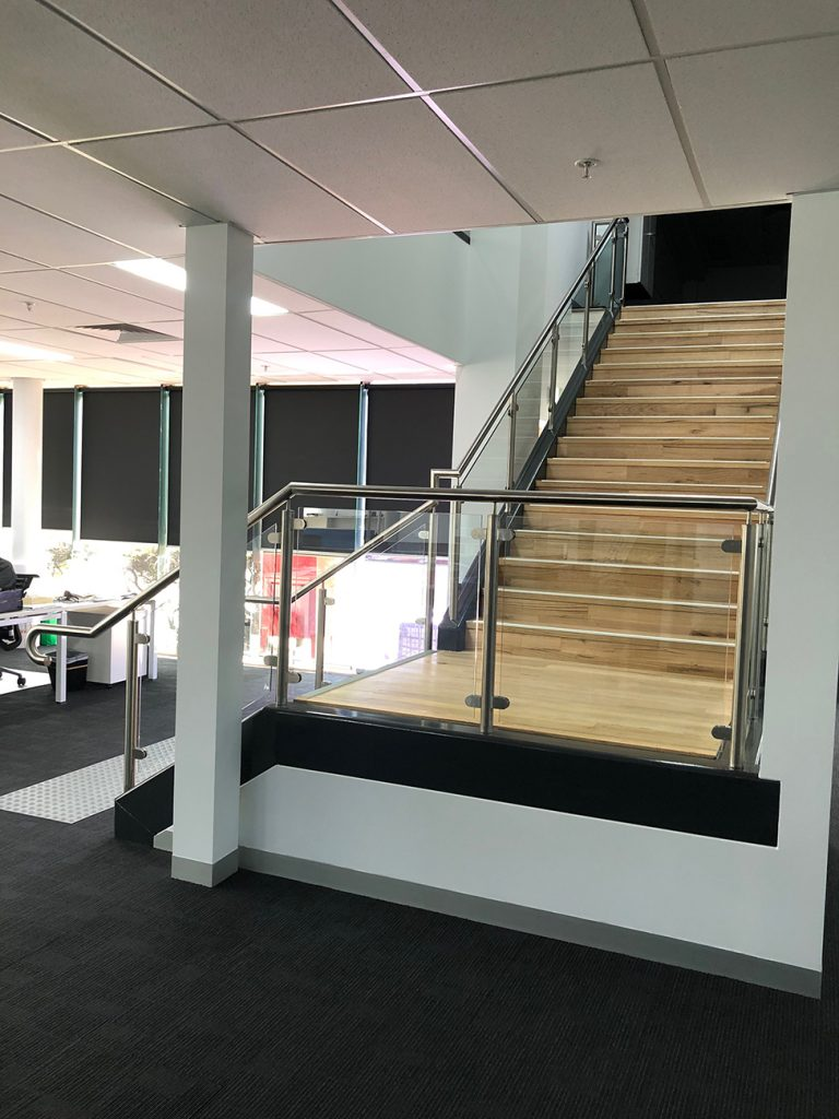 View from bottom of wood staircase in office with metal hand railing and glass panels