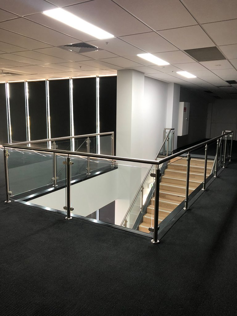 View from top of wood staircase in office with metal hand railing and glass panels