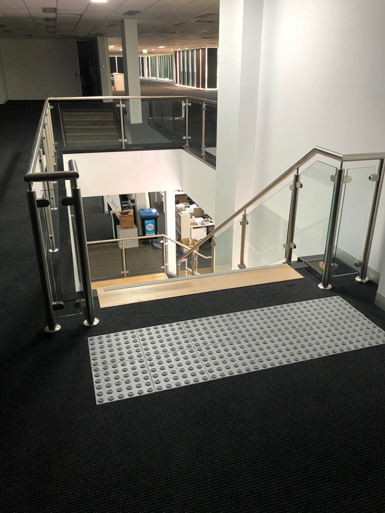 View from top of wood staircase with rubber foot mat