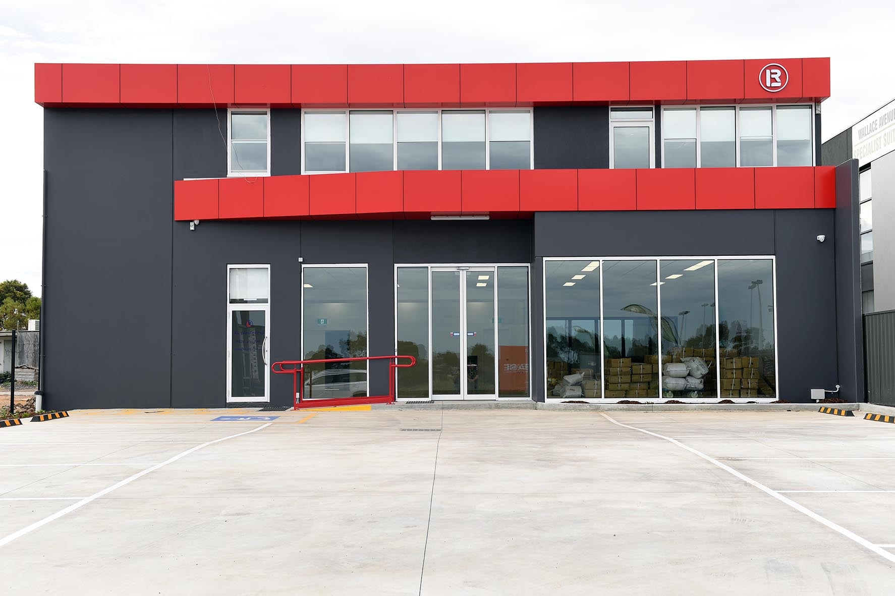 red and grey precast concrete walls and large glass windows at front of building