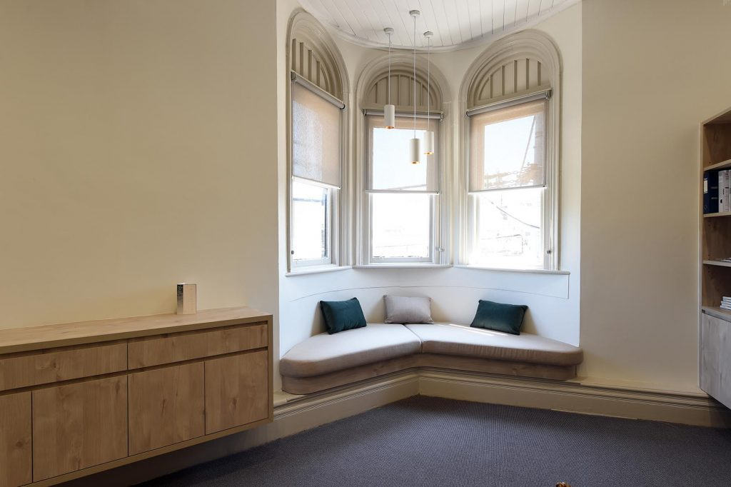 Casual meeting room in corner of building with heritage windows