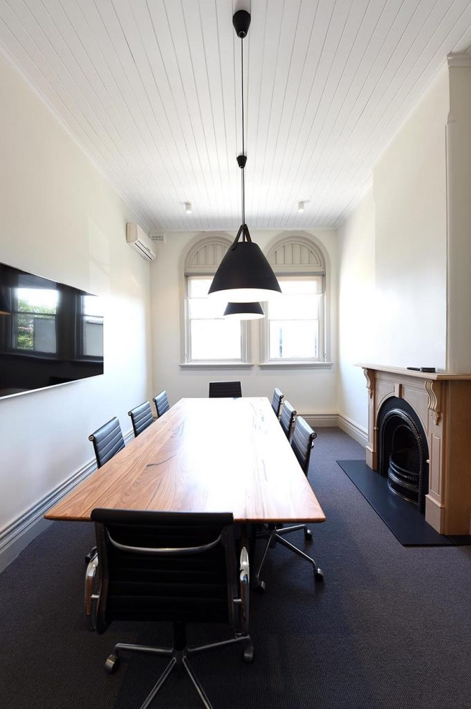 Meeting room with solid wooden table surrounded by black office chairs and a fireplace to the right