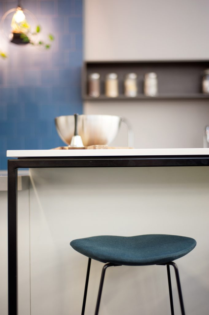 Blue stool in front of kitchen bench with feature wall in background