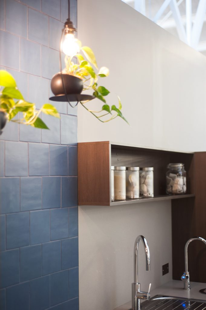 Blue feature tile wall beside kitchen sink and wooden joinery cupboards