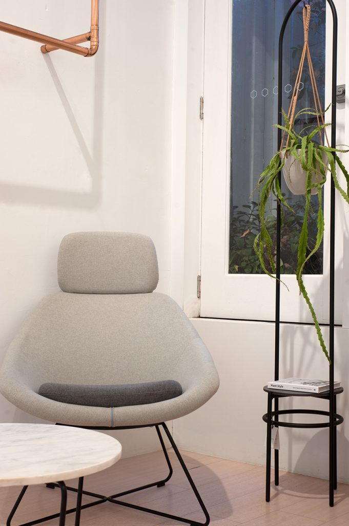 Modern design chair in front of window with hanging plant on the right