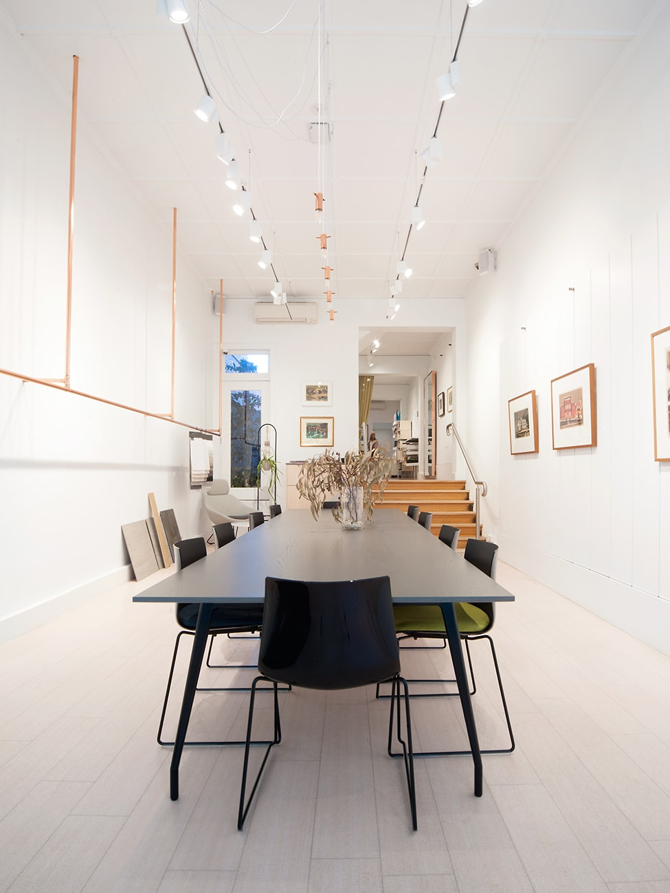 Long meeting table in a white walled room