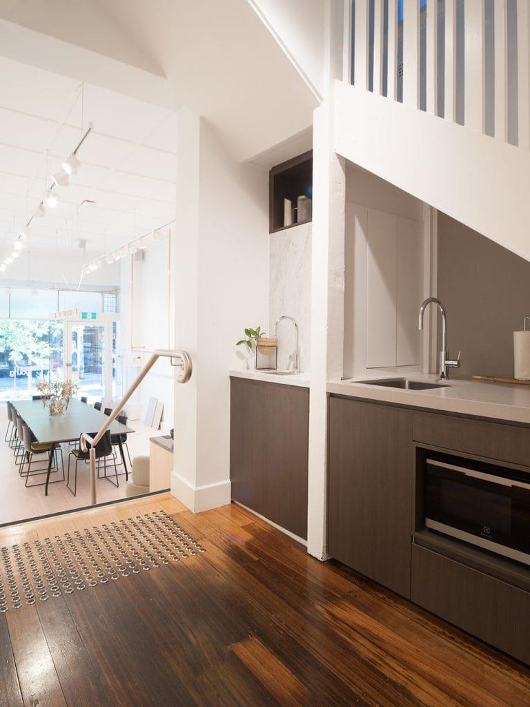 Hardwood floors beneath white staircase